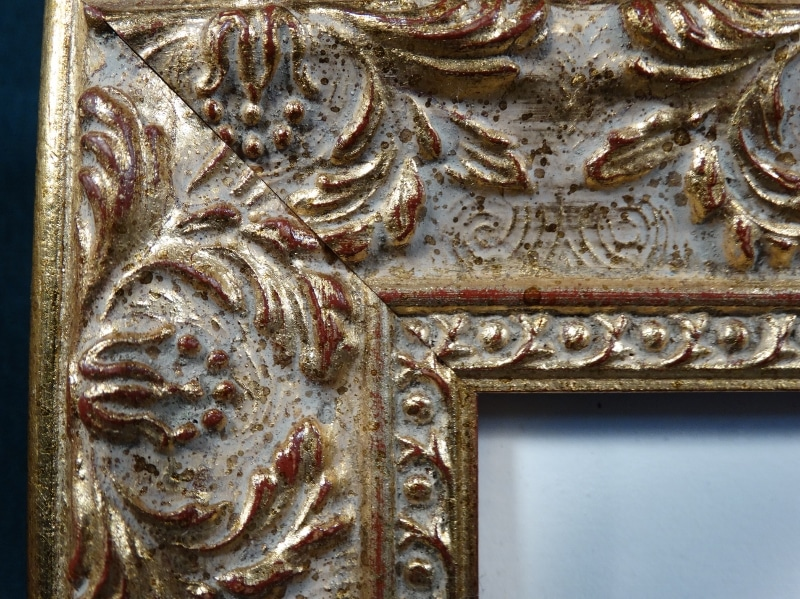 luxurious picture frame with ornate details and gold leafing over red paint.