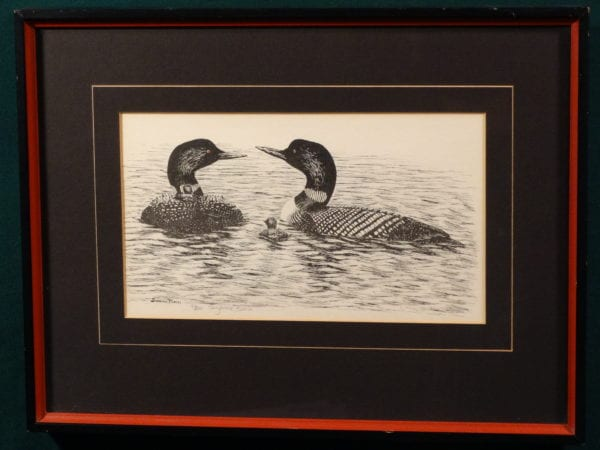 framed piece of loon artwork signed by artist.